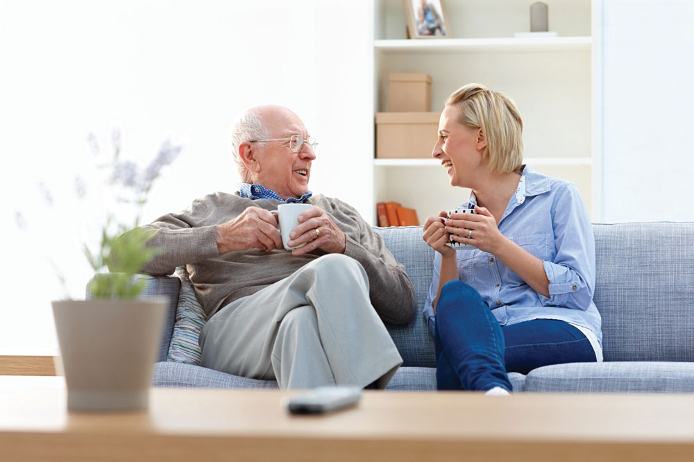 Charter Senior Living of Bay City Resident enjoys a cup of tea with granddaughter on blue couch